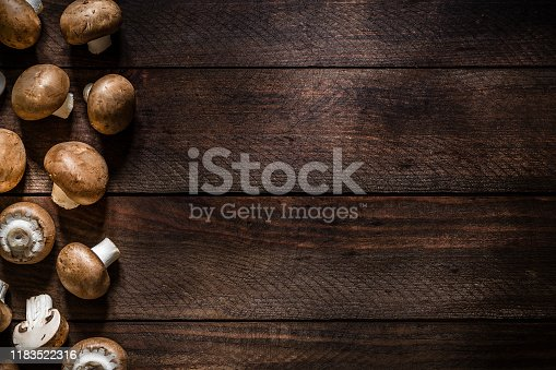 Top view of a various Cremini mushrooms on a rustic wooden table. The mushrooms are at the left border of the image so there is a useful copy space at the right side. Low key DSLR photo taken with Canon EOS 6D Mark II and Canon EF 24-105 mm f/4L