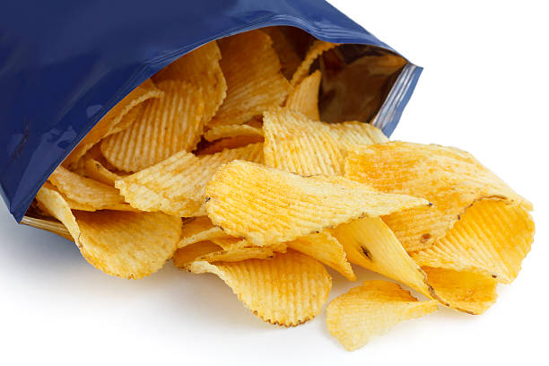 crinkle cut crisps spilling out of a foil packet. - crisp packet stock photos and pictures