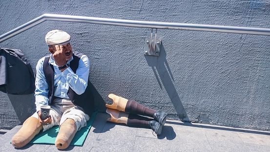 Istanbul, Turkey - April 21, 2016: maleformation of a mature male person on side of the street for helping panhandler aid human relations street city life concepts