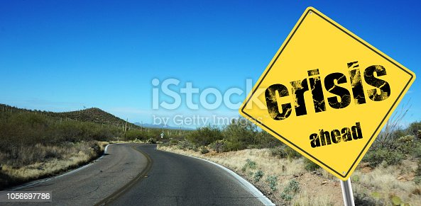 Crisis ahead sign on a sky background and dessert road