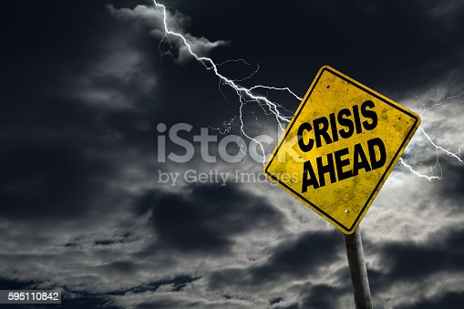 Crisis Ahead sign against a stormy background with lightning and copy space. Dirty and angled sign adds to the drama. Concept of political, financial, social, health crisis, etc.
