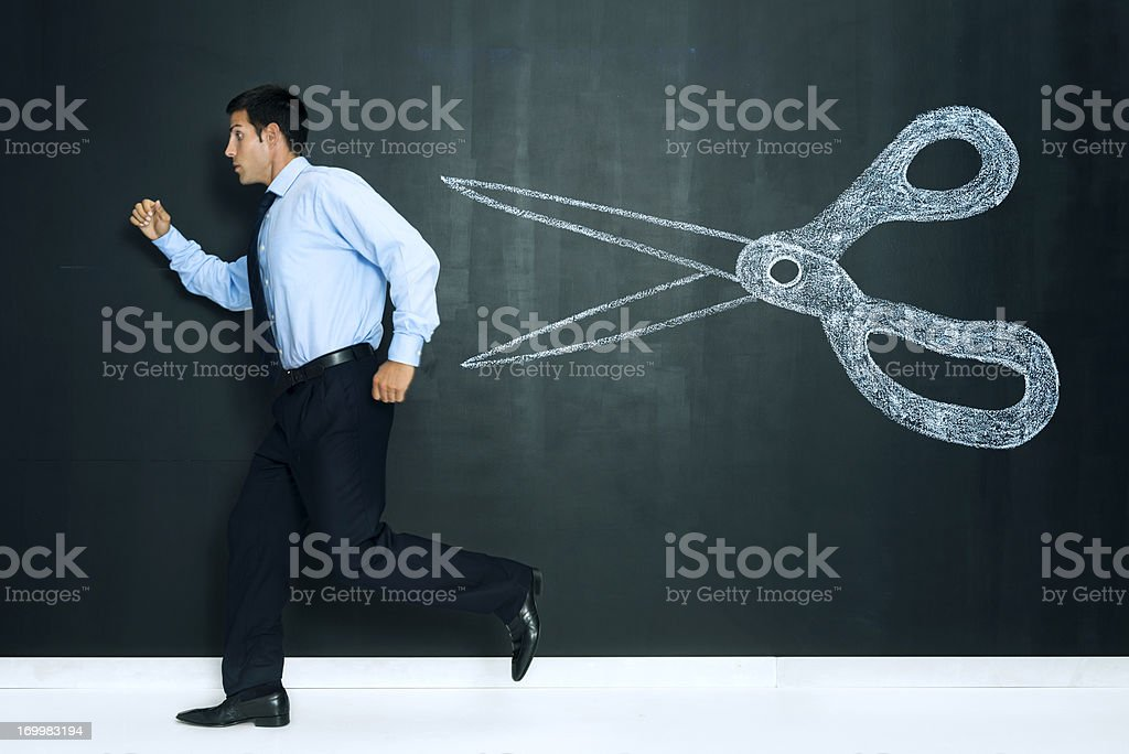 Crisis: businessman escaping from big cuts stock photo