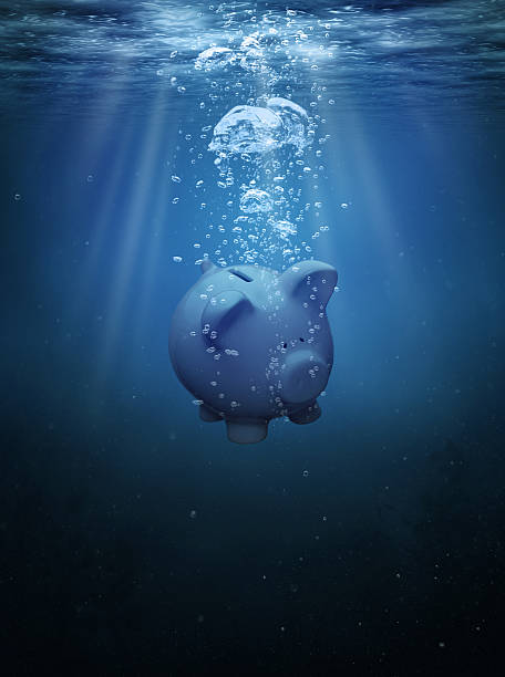 Crisis concept Piggy bank drowning in the ocean with copy space sunken stock pictures, royalty-free photos & images