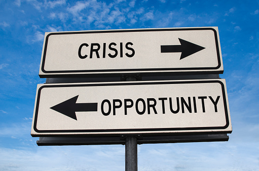 Crisis vs opportunity. White two street signs with arrow on metal pole with words. Directional road. Crossroads Road Sign, Two Arrow on blue sky background. Two way road sign with text.