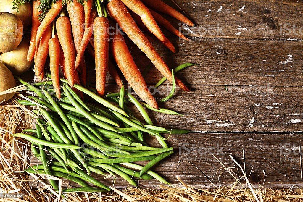Crisp carrots and green beans on weathered wood background royalty-free stock photo