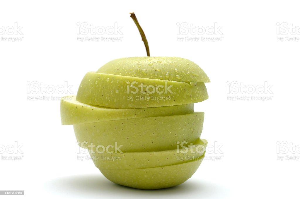 crisp green apple sliced jigsaw covered in water droplets royalty-free stock photo