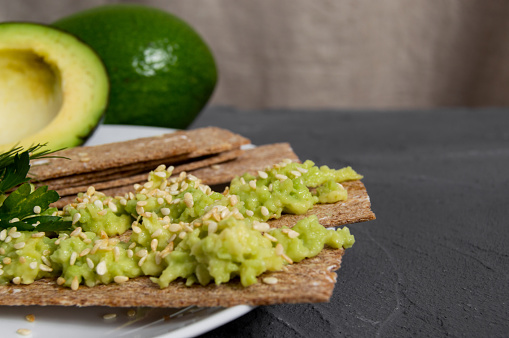 Crispbreads with mashed avocado sprinkled sesame seed on plate