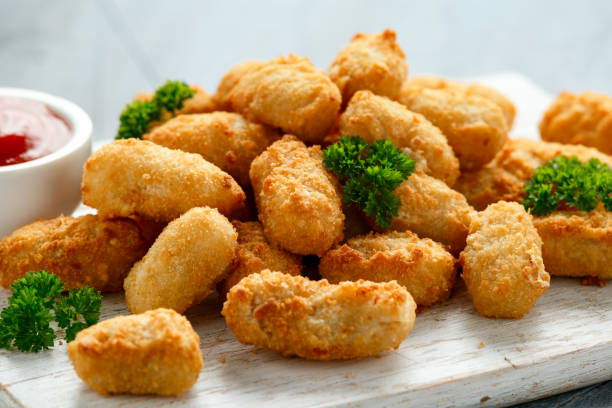 Crispy Battered scampi nuggets with ketchup on white wooden board stock photo