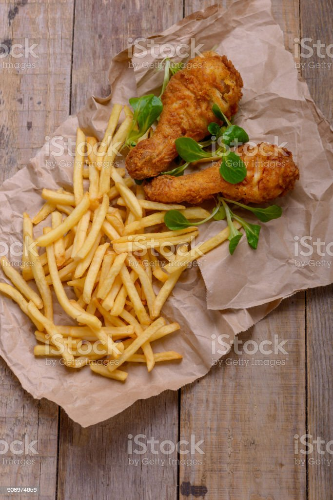 Crispy chicken legs and french fries stock photo