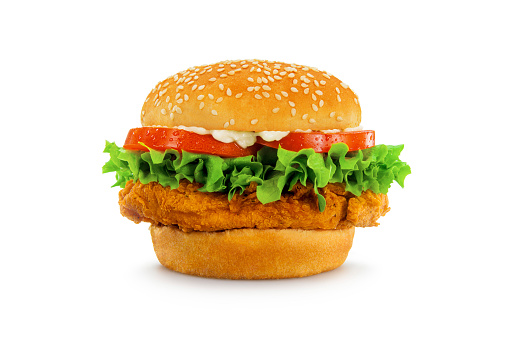 A crispy chicken sandwich, perfectly proportioned and styled, shot in an aspirational fast food advertising style and isolated on white. Sesame seed bun, visible condensation on tomatoes, lettuce, and mayo.