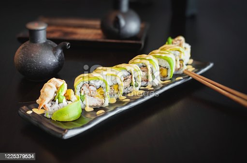 Crispy crab sushi roll with asparagus, mango wrapped in thin fresh avocado and sweet sour sauce