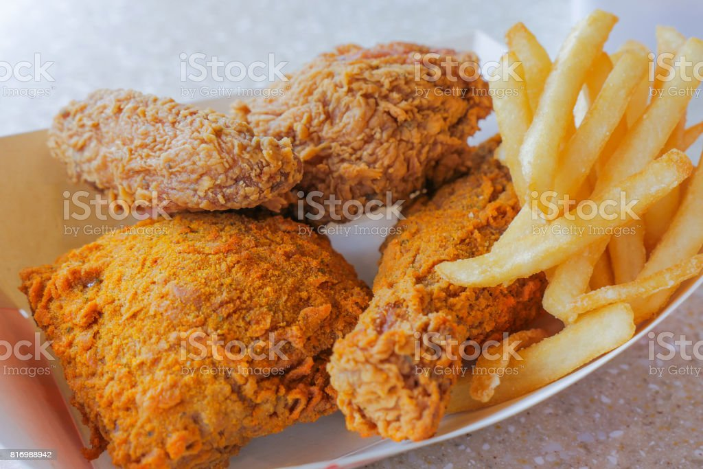 crispy deep fried chicken and french fries, unhealthy eating stock photo