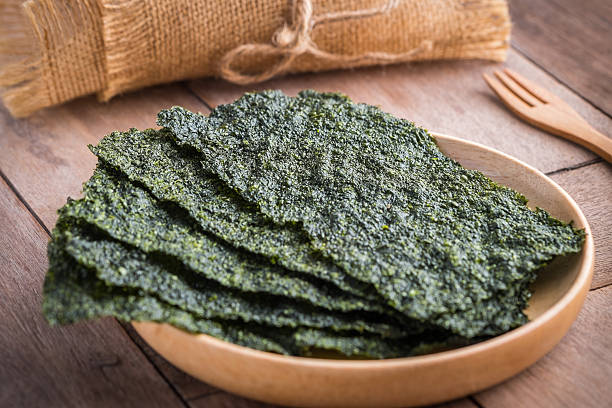 crispy dried seaweed on wooden plate - zeewier stockfoto's en -beelden