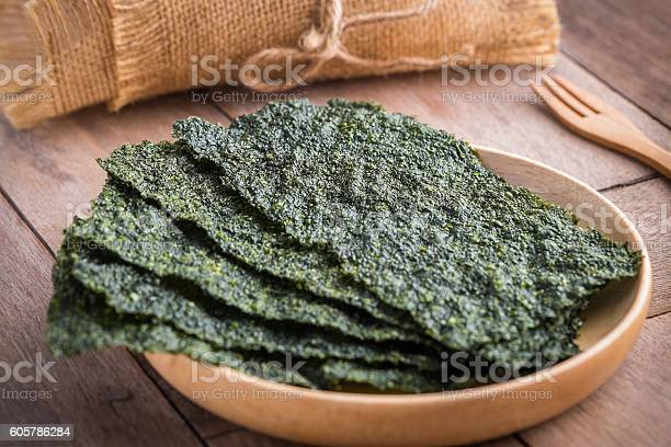 Photo of Crispy dried seaweed on wooden plate