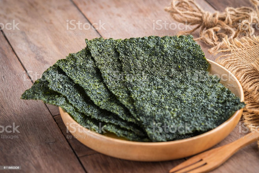 Crispy dried seaweed on wooden plate - foto de stock