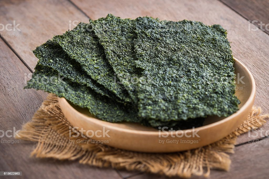 Crispy dried seaweed on wooden plate stock photo
