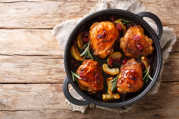 Crispy fragrant baked chicken thighs with apples, cranberries and rosemary closeup in a pan on the table. horizontal top view stock photo