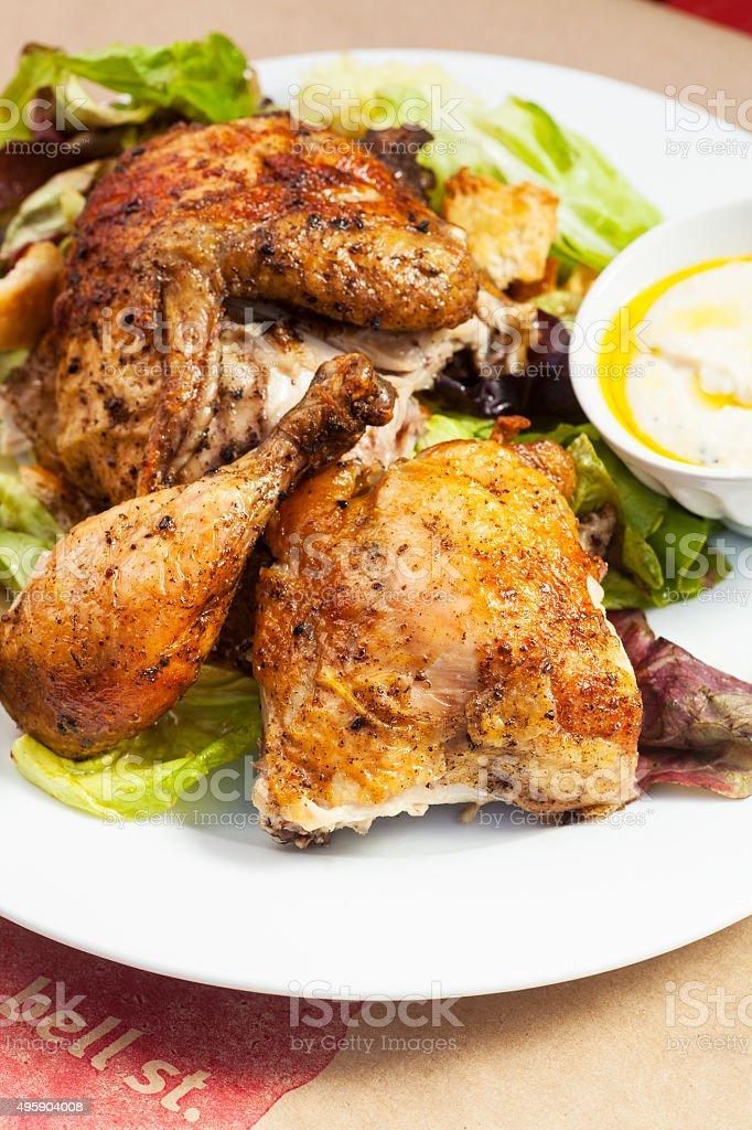 crispy free-range rotisserie chicken on organic butterleaf salad stock photo