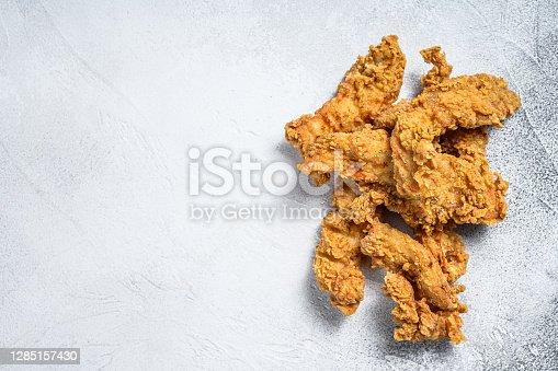 Crispy fried breaded chicken breast strips. White background. Top view. Copy space.