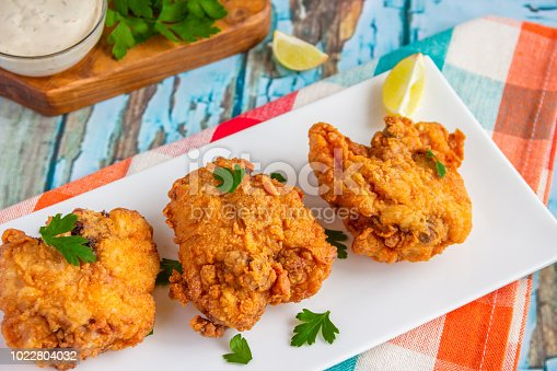Crispy fried chicken with lemon and parsley served in a white platter