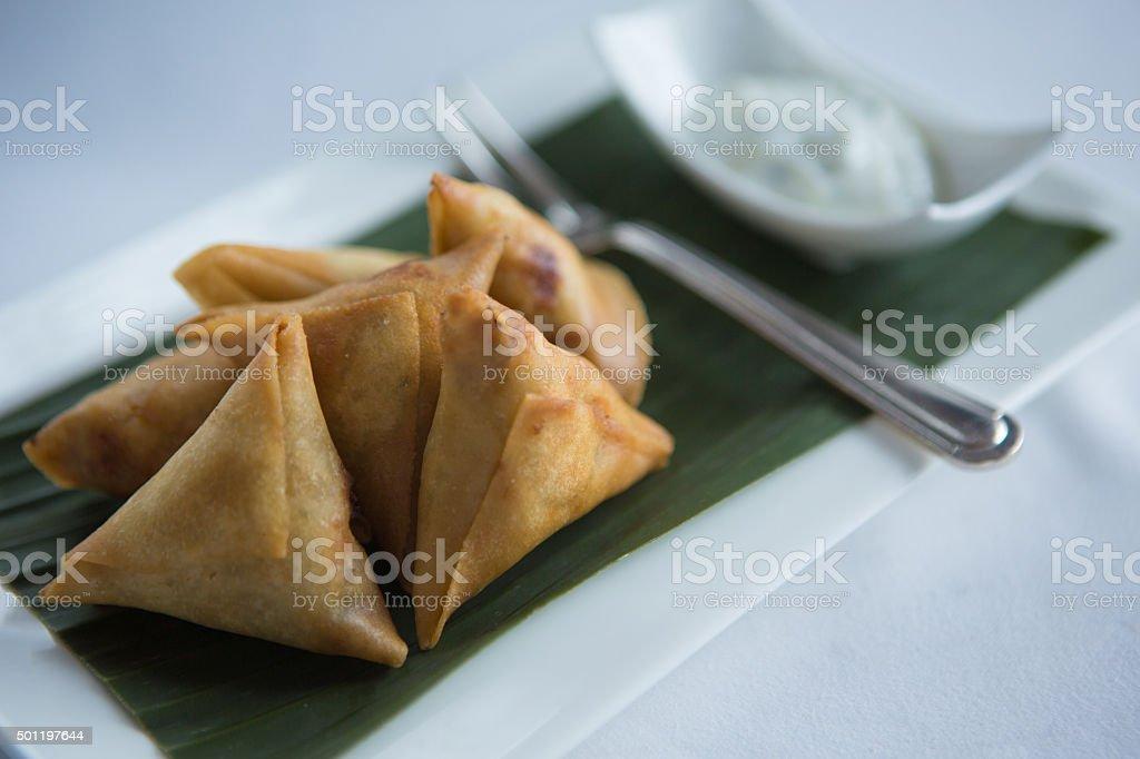 Crispy fried Chicken samosas with yogurt dipping sauce. stock photo