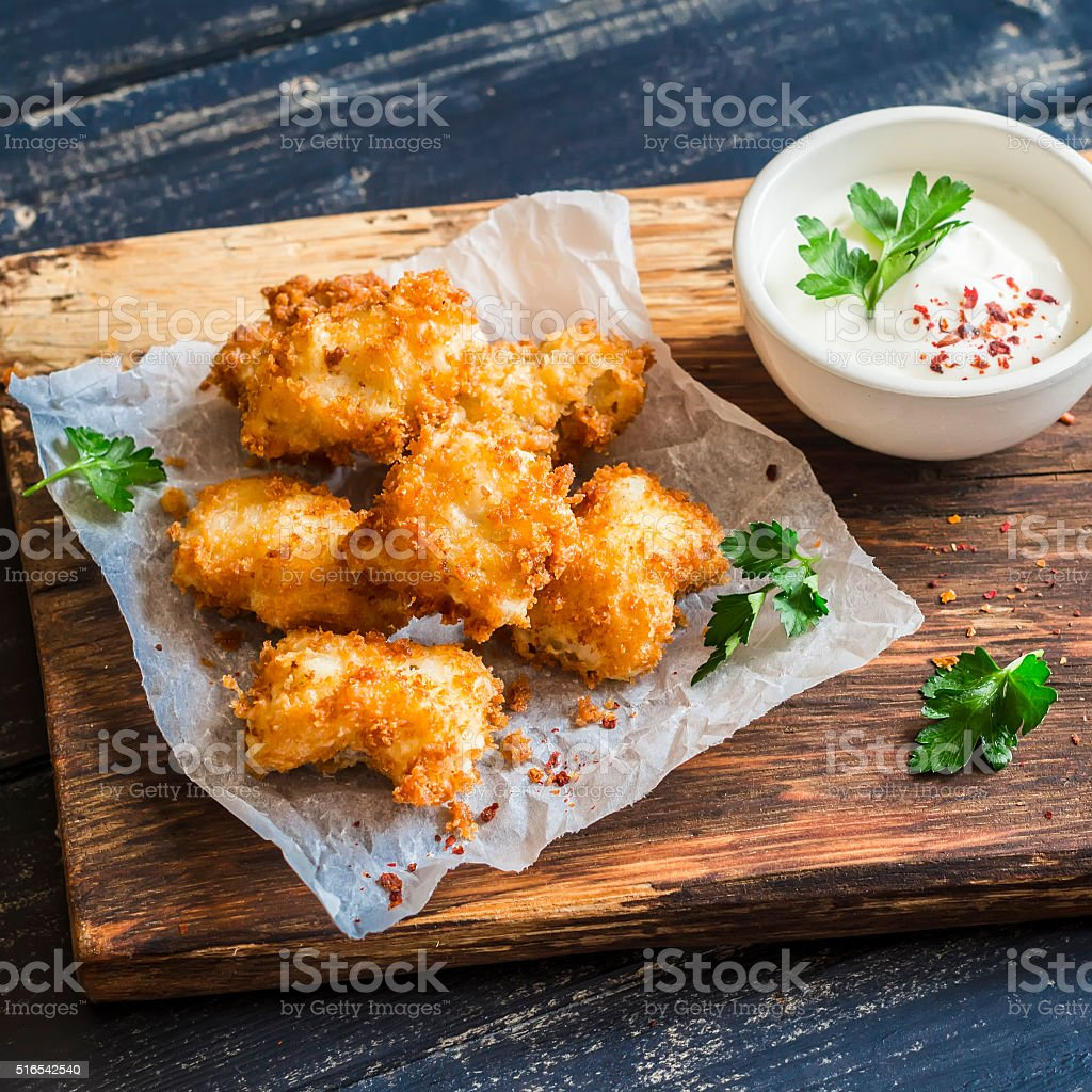 Crispy fried fish on a wooden rustic board stock photo