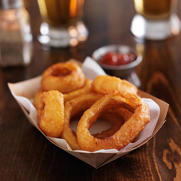crispy fried onion rings in disposable tray - gefrituurde uienring stockfoto's en -beelden