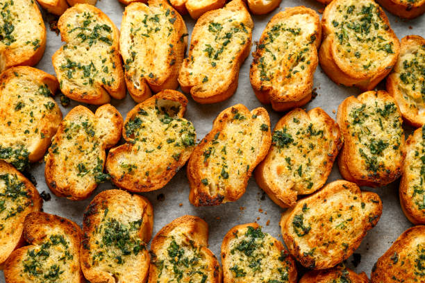 Crispy Garlic bread with herbs on baking paper stock photo