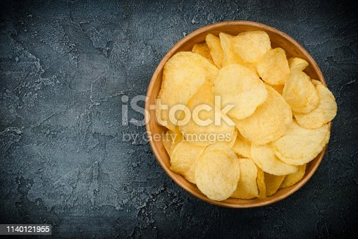 Crispy potato chips in bowl on dark rustic table. Overhead view with copy space.