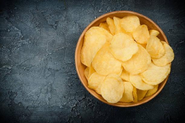 在黑暗的鄉村桌子上的碗裡的脆脆土豆片 - 薯片 個照片及圖片檔