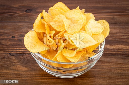 Crispy potato chips in bowl on wooden background.