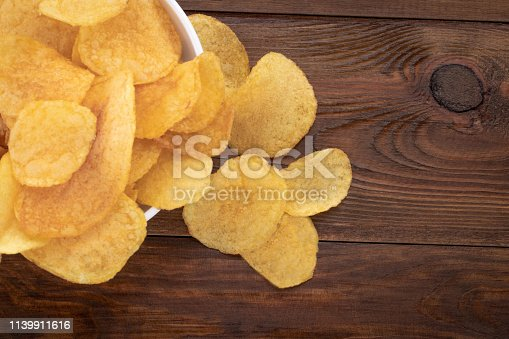 Crispy potato chips in bowl on wooden background, top view.