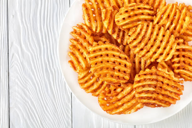 Crispy Potato Waffles Fries, flat lay Crispy Potato Waffles Fries, Wavy, Crinkle Cut, Criss Cross Fries on a white plate on a wooden table, view from above, close-up, flat lay waffle stock pictures, royalty-free photos & images