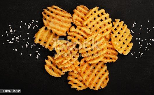 Crispy potato waffles fries, wavy, crinkle cut, criss cross cries on black background