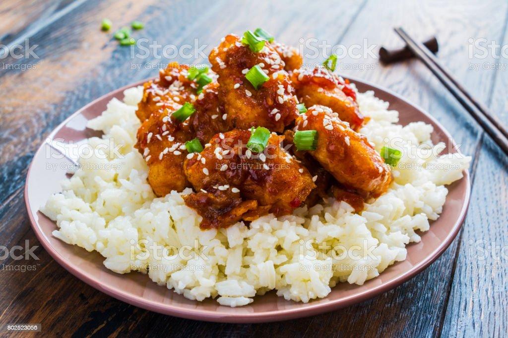 Pollo de sésamo crujiente, picado filetes de pechuga, con un dulce pegajoso salsa asiática y arroz blanco cocido en un plato en la mesa de madera. - foto de stock