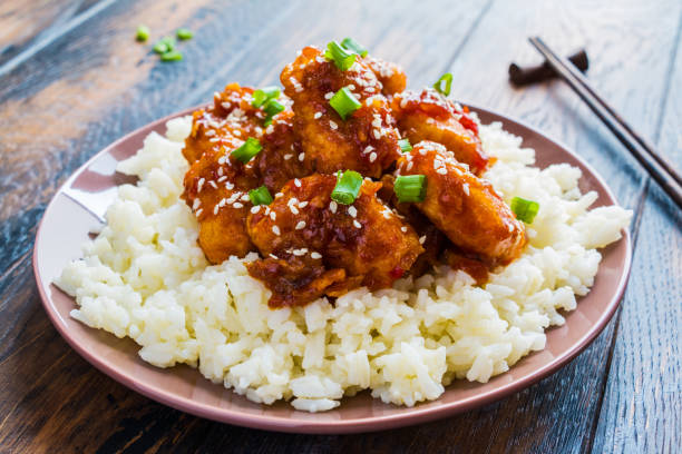 crispy sesame chicken, chopped breast fillets, with a sticky sweet asian sauce and white boiled rice on a plate on wooden table. - chinese food stock photos and pictures