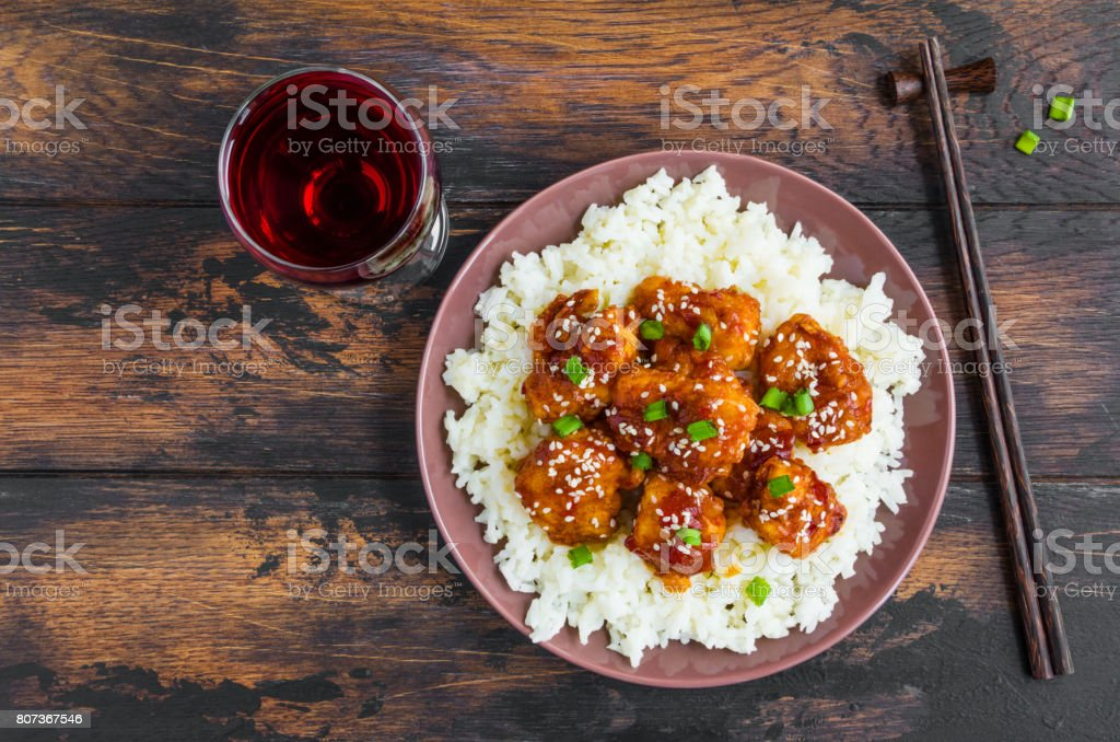 Crispy sesame chicken, chopped breast fillets, with a sticky sweet Asian sauce and white boiled rice on a plate on wooden table, top view. stock photo