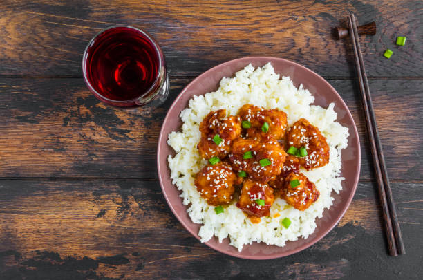 crispy sesame chicken, chopped breast fillets, with a sticky sweet asian sauce and white boiled rice on a plate on wooden table, top view. - sesame stock photos and pictures