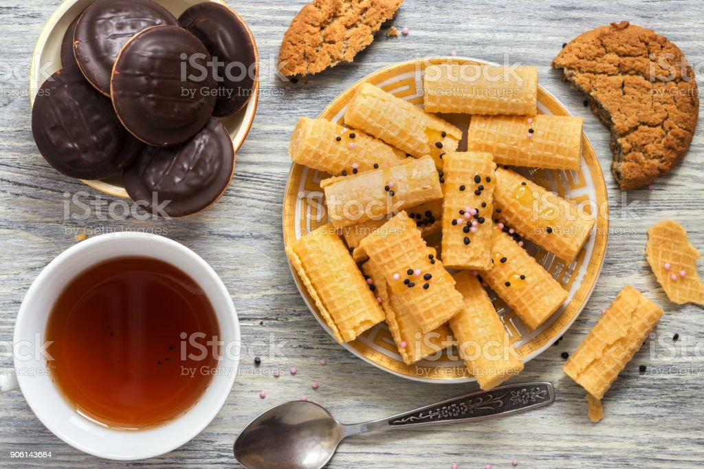 Crispy wafer rolls in a plate with tea and chocolate chip cookies, top view. stock photo