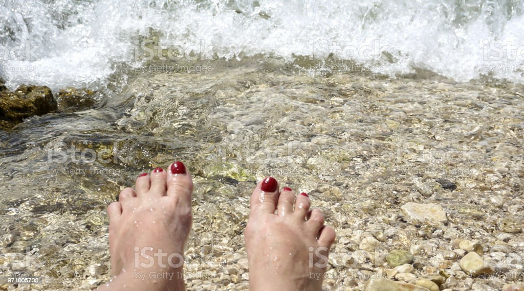 Cristal clear sea waves on the pebble beach and woman toes at the bottom of the picture stock photo