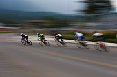 A group of male bicycle racers ride together during a criterium road bike race.  A criterium road bike race is an event where competitors do several laps around a closed circuit usually in a city or urban center.