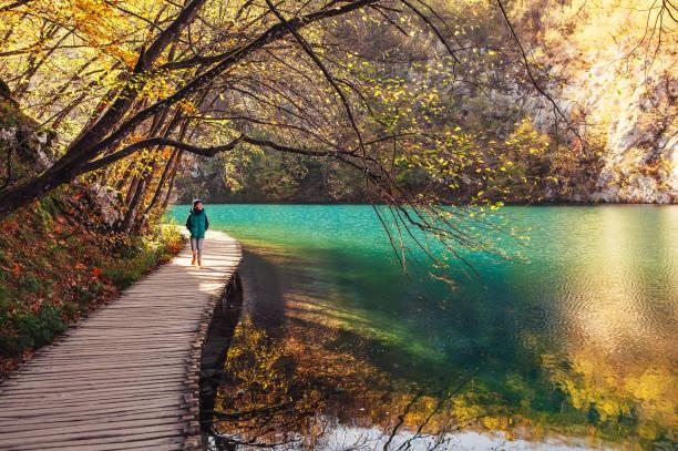 kroatien nationalpark plitvicer seen im herbst - spaziergänge junge auf der brücke über den see - nationalpark plitvicer seen stock-fotos und bilder