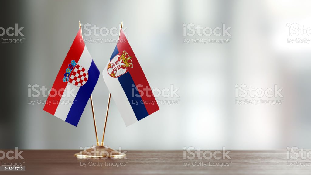 Croatian And Serbian Flag Pair On A Desk Over Defocused Background - fotografia de stock