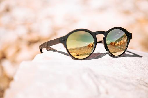 Sunny croatian mediterranean beach mirroring in black sunglasses. Selective Focus Detail Shot. Dalmatia, Croatia, Southeast Europe.