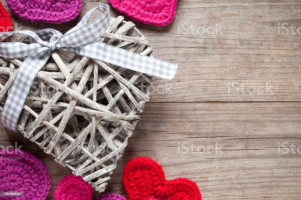 Crochet and wicker hearts on wooden table stock photo