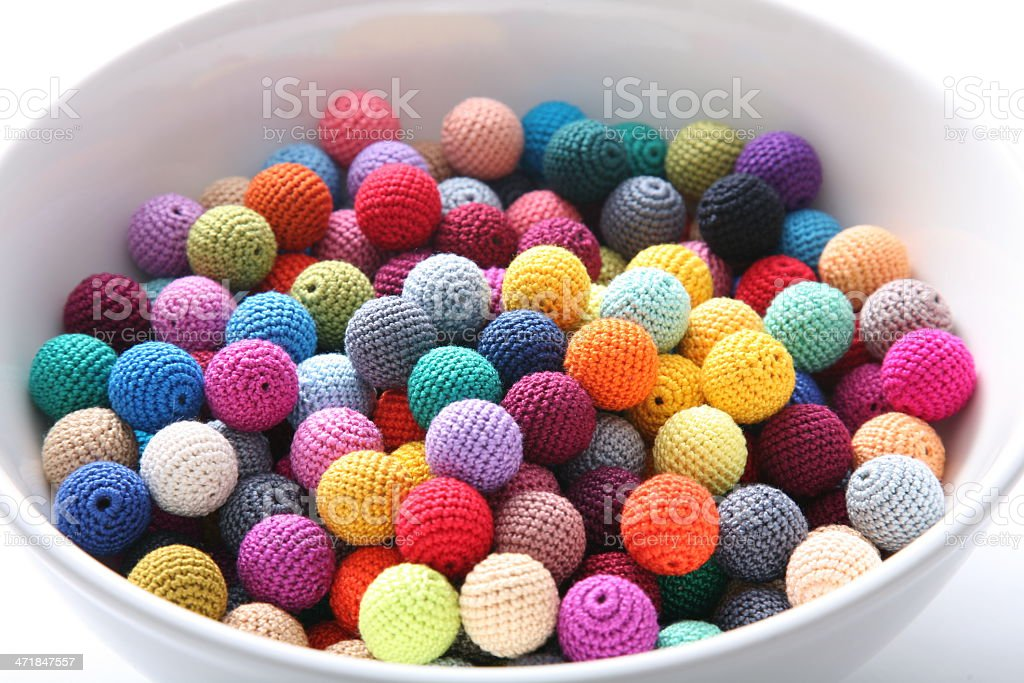 Crochet beads balls in white bowl close-up royalty-free stock photo