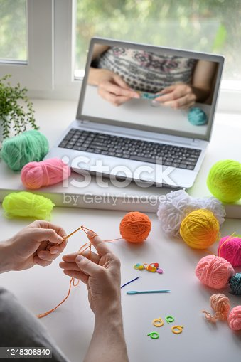 crocheting with brown wool in hand.