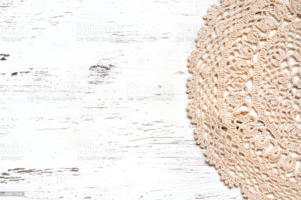 Crochet doily border over shabby chic wood stock photo