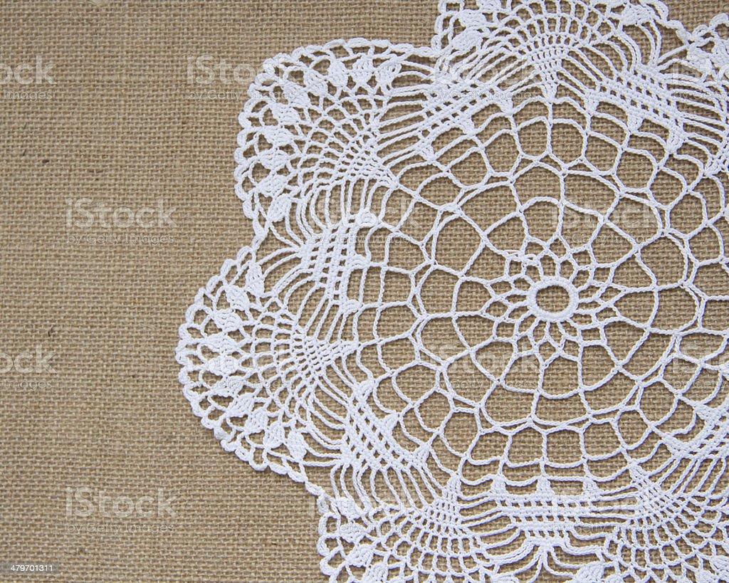 Crochet doily over burlap stock photo