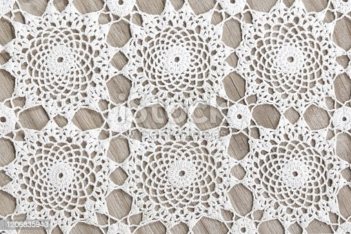 istock crochet doily, tradional circle knitting background, on a wooden table 1206835943
